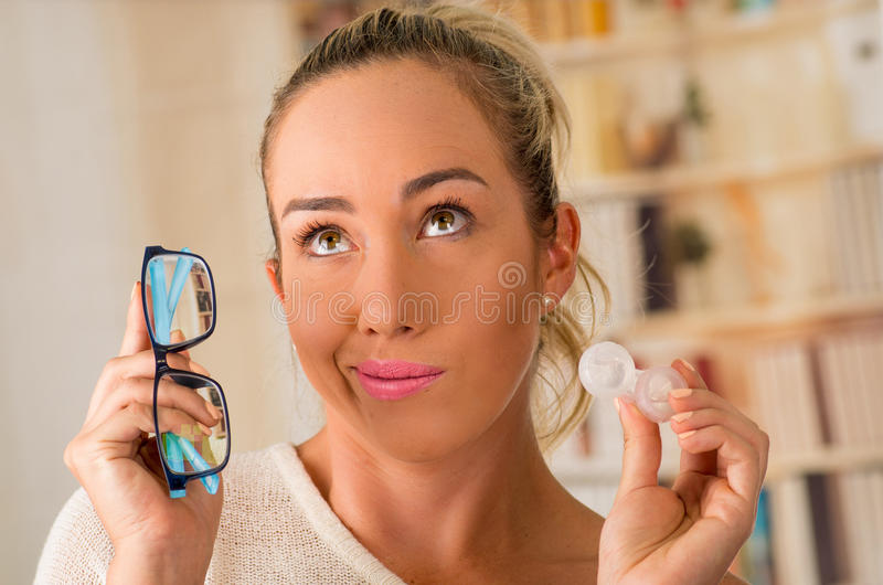 Young blonde woman holding contact lens case on hand and holding in her other hand a blue glasses on blurred background. Eyesight and eyecare concept stock photo