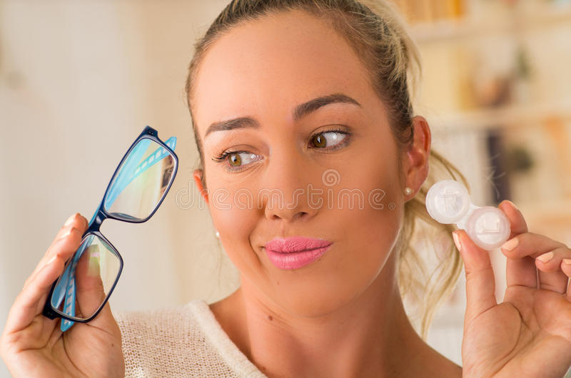 Young blonde woman holding contact lens case on hand and holding in her other hand a blue glasses on blurred background. Eyesight and eyecare concept royalty free stock images