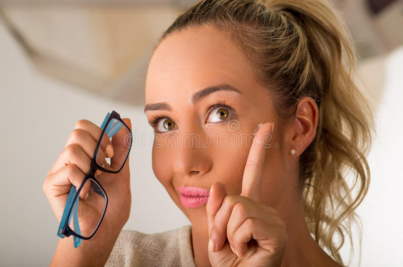 Young blonde woman holding contact lens on finger in front of her face and holding in her other hand a blue glasses on. White background., eyesight and eyecare royalty free stock photography