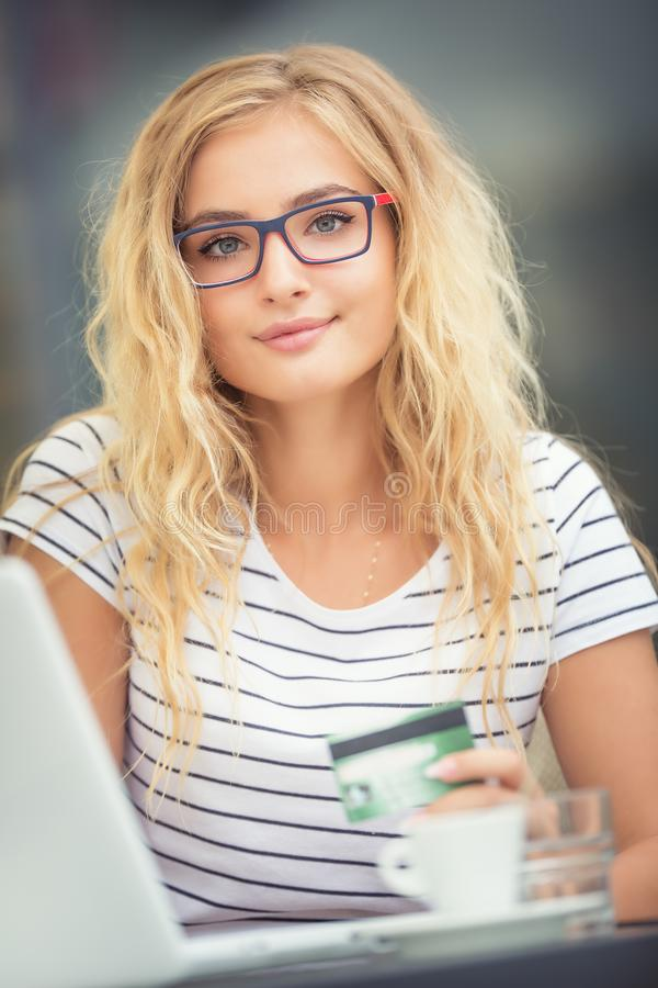 Young blonde woman holding credit card and using laptop computeron the terrace of the caf. Pay, internet, online, girl, people, business, cafe, female, coffee royalty free stock photography