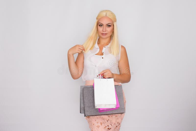 Young blonde woman holding shopping bags in hands royalty free stock images