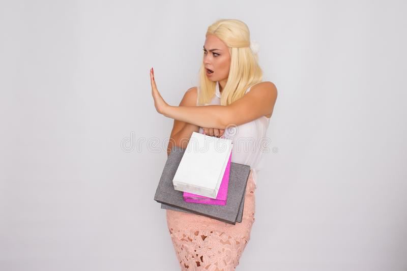 Young blonde woman holding shopping bags in hands royalty free stock image