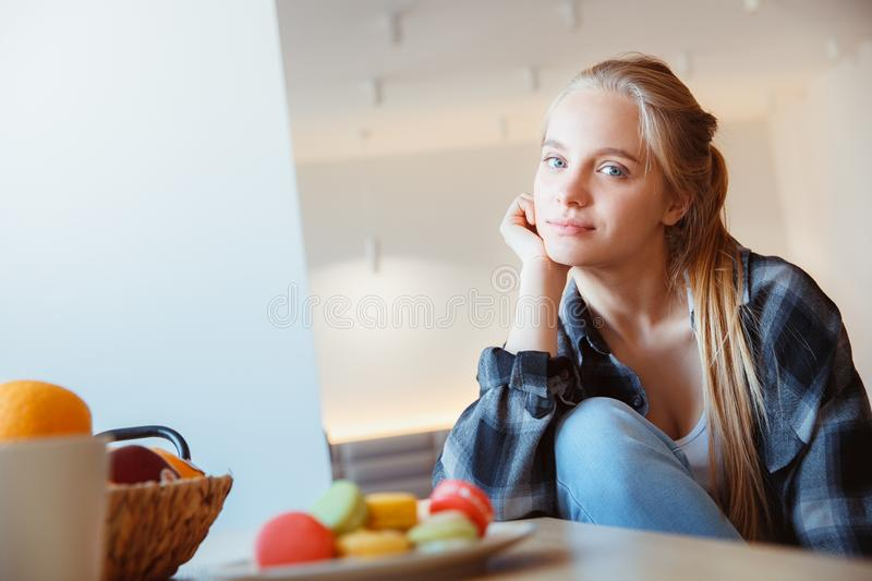 Young woman at home in the kitchen drinking tea bored stock photography