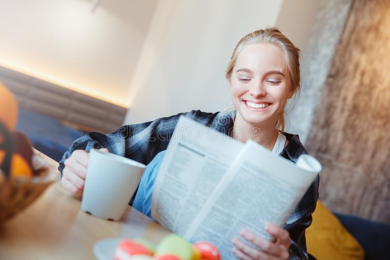 Young woman at home in the kitchen drinking tea reading newspaper stock photos