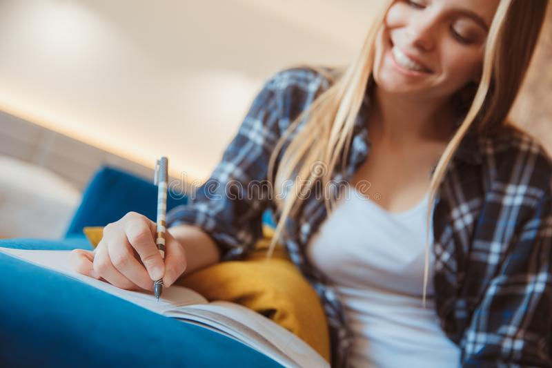 Young woman at home in the living room taking notes close-up royalty free stock image