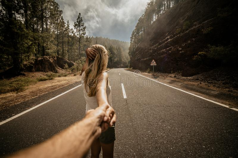 Young blonde woman leading a man by hand on empty road along the forrest. Summer time. Lifestyle. Follow me. View from behind. stock image
