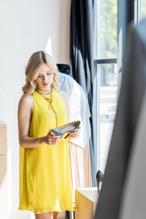 young blonde woman looking at high heel shoes stock photography