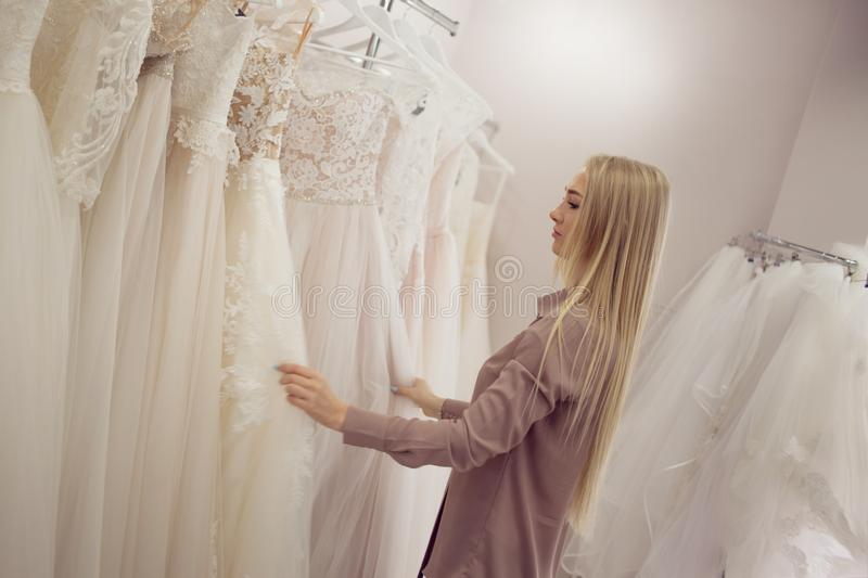 Young blonde woman looks different dress on the hanger. Bridal shop. stock image