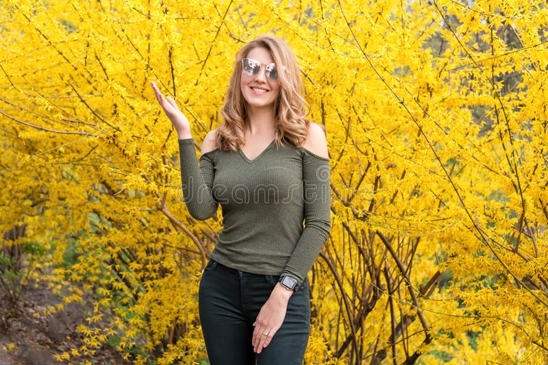 Young blonde woman near blossoming yellow trees in spring park on sunny day. Beautiful happy girl enjoying smell in a stock photography