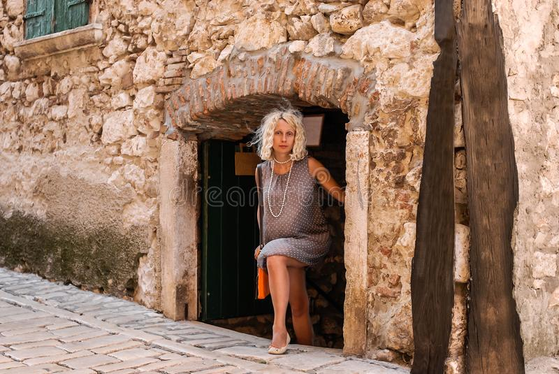 A young blonde woman in a neutral gray dress goes out of a doorway to a street. royalty free stock images