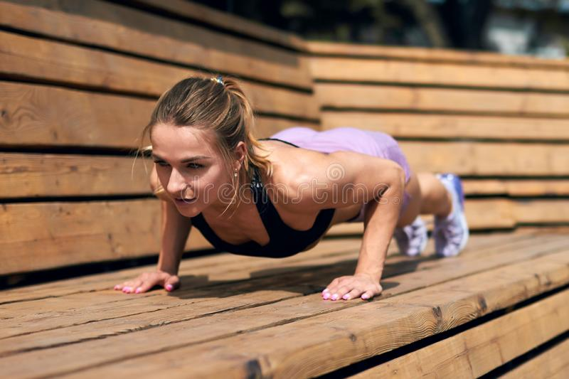 Young blonde woman practicing yoga. Doing Push ups or press ups exercise, working out in the street, full length photo.lifestyle concept.motivation concept stock image