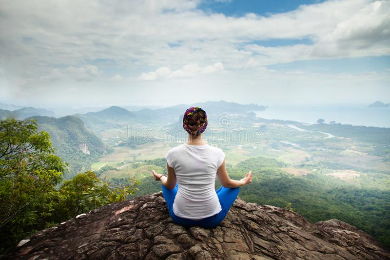 Young blonde woman practicing yoga and meditation in mountains during luxury yoga retreat in Bali, Asia stock photo