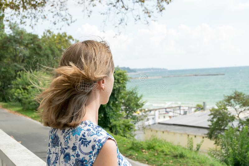 Blonde with curly hair in the wind looks at the sea. Young blonde woman on a promenade of Varna in Bulgaria. Curly hair in the wind. Black Sea coast at royalty free stock photography