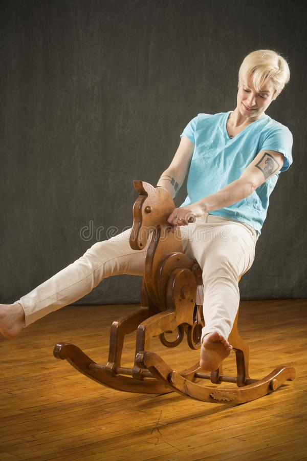 Free Young Blonde Woman Riding Wooden Rocking Horse In The Studio. Royalty Free Stock Images - 111287489