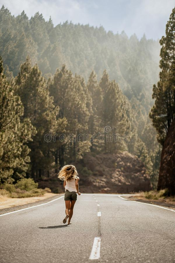Young blonde woman running in flip flops on empty road along the forrest. Summer time. Lifestyle. Follow me. View from behind. royalty free stock photography