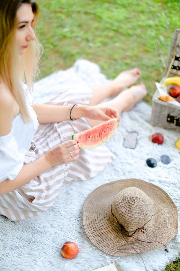 Young blonde woman sitting on plaid near fruits and hat, eating watermelon, grass in background. royalty free stock photo