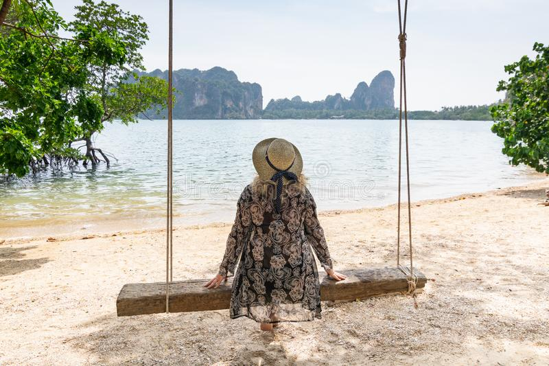 Young blonde woman sitting on a wooden swing at Krabi Railey beach overlooking the harbour and mountains, Thailand.  stock photography
