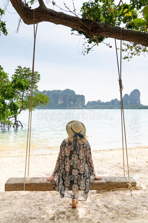 Young blonde woman sitting on a wooden swing at Krabi Railey beach overlooking the harbour and mountains, Thailand. Vertical orientation stock photography