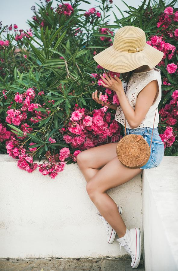 Young blonde woman smelling blooming oleander tree stock photos