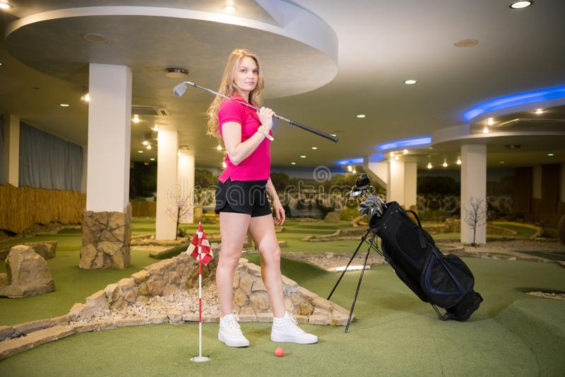 A young blonde woman standing in golf club near the stick bag holding a golf stick. Posing stock photo