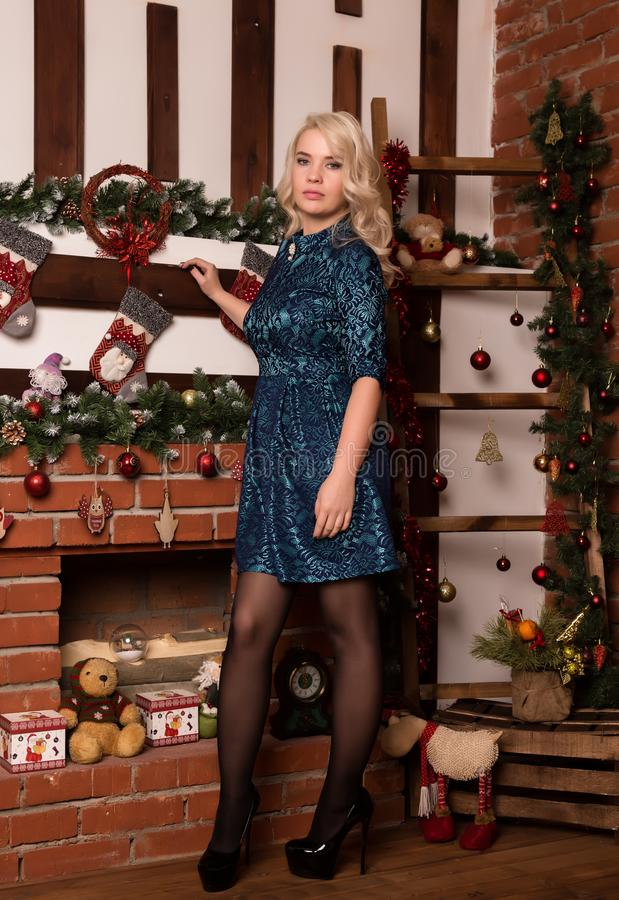 Young blonde woman standing near fireplace at home winter concept royalty free stock image