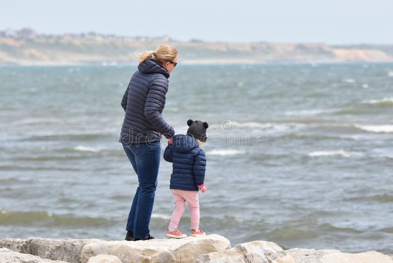 Mother holding the hand of a young child at the ocean edge. Dorset, UK. May 2018 royalty free stock photography