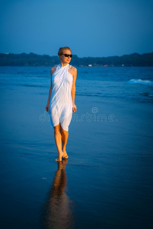 Young blonde woman in sunglasses walks barefoot along the surf on the sea on a warm summer evening. Soft light at sunset, blue sea. Reflection on wet sand stock photo