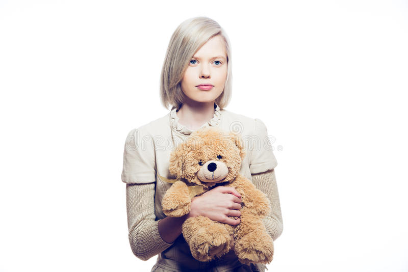 Young blonde woman with teddy bear. Light background royalty free stock images