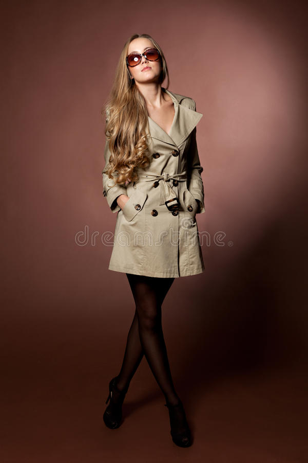 Young blonde woman in topcoat.