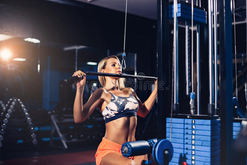 Woman training with weight-lifting training machine. Young blonde Woman training back with weight-lifting training machine stock images