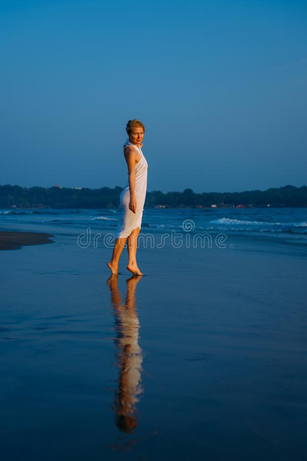 Young blonde woman walks barefoot along the surf on the sea on a warm summer evening. Soft light at sunset, blue sea, reflection. On wet sand stock image