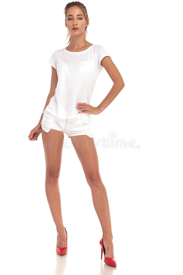 Young blonde woman in white shorts and shirt. Posing in studio royalty free stock photo