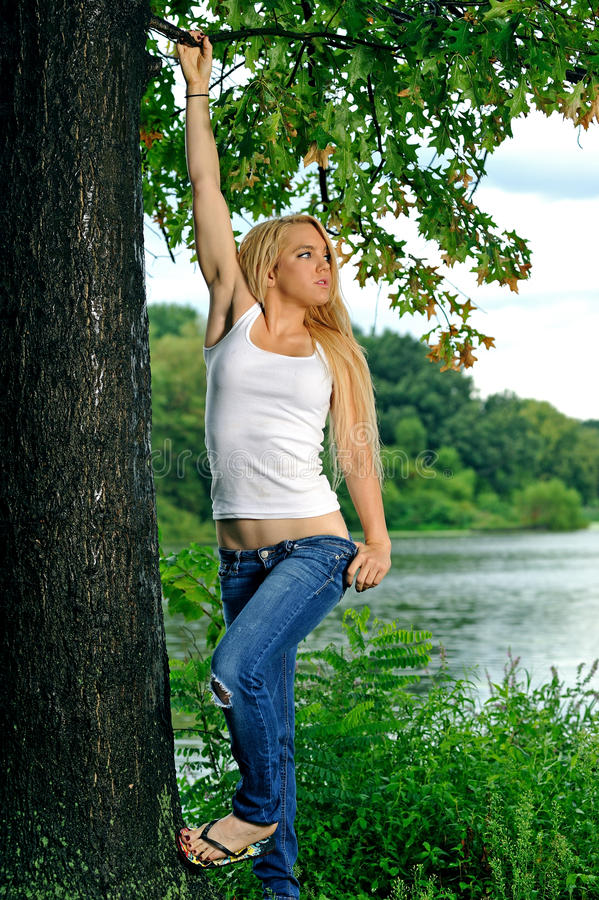 Young Blonde Woman In White Tank Top And Jeans Stock Photo