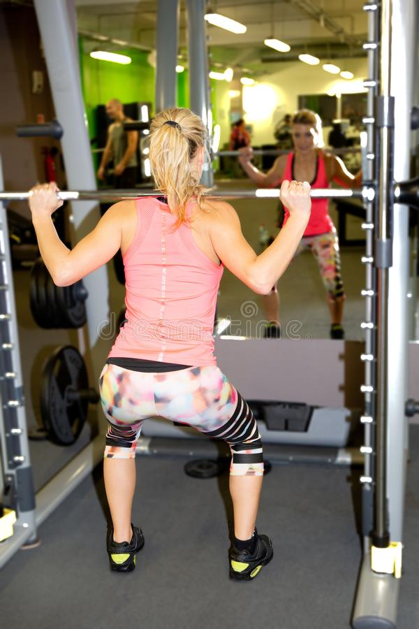 Young blonde woman working at the lat pulldown machine in the gym stock photos