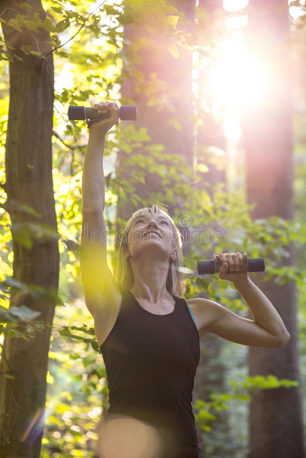 Young blonde woman working out with dumbbells outside in forested area royalty free stock photography
