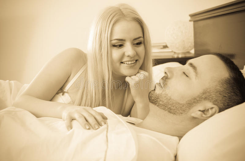 Young blondie and sleeping boyfriend. Portrait of smiling young blondie looking at sleeping boyfriend in bedroom stock images