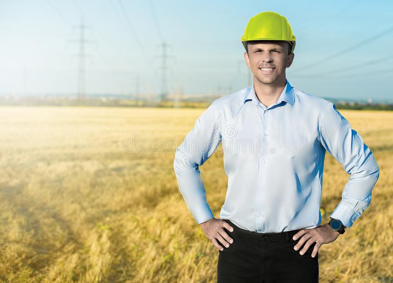 Young blue collar worker or engineer wearing in yellow helmet stands in the field with wide smile. stock photos