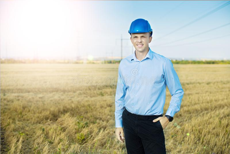 Young blue collar worker or engineer wearing in yellow helmet stands in the field with wide smile. royalty free stock images