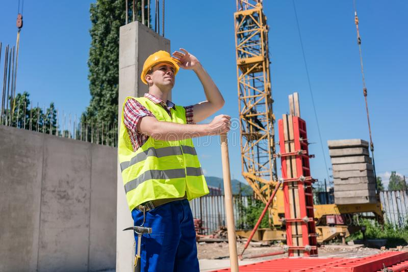 Young blue-collar worker looking up with a worried facial expression stock photos