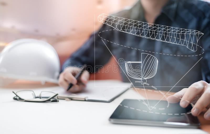 Young blurred sub-designer sitting in the office and designing ship for future construction, with digital drawing on tablet PC. royalty free stock photo