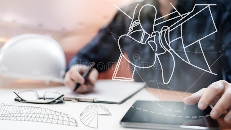 Young blurred sub-designer sitting in the office and designing ship for future construction, with digital drawing on tablet PC. Young blurred sub-designer royalty free stock image