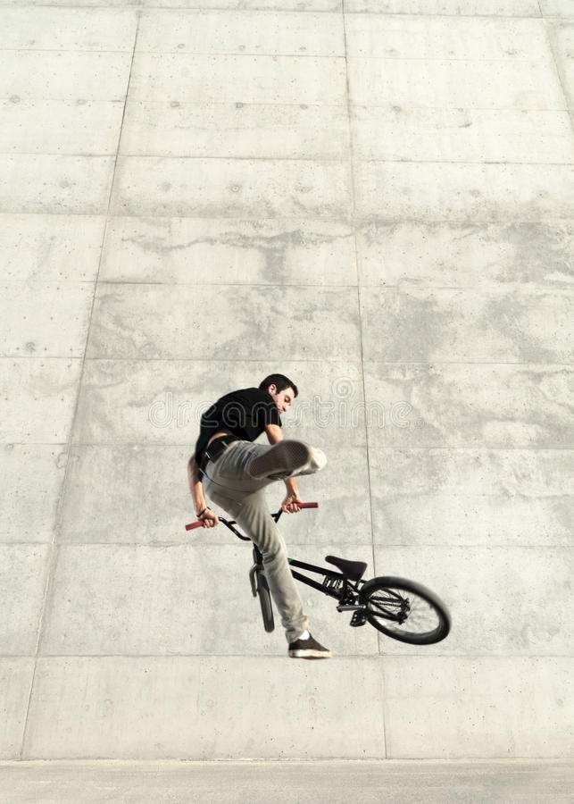 Young BMX bicycle rider. On a grey urban concrete background stock photo