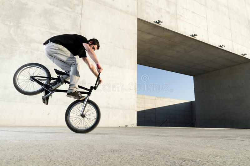Young BMX bicycle rider. On a grey urban concrete background stock images