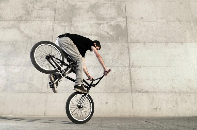 Young BMX bicycle rider. On a grey urban concrete background royalty free stock photo
