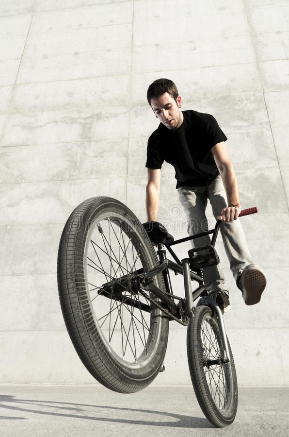 Young BMX bicycle rider. On a grey urban concrete background royalty free stock photography