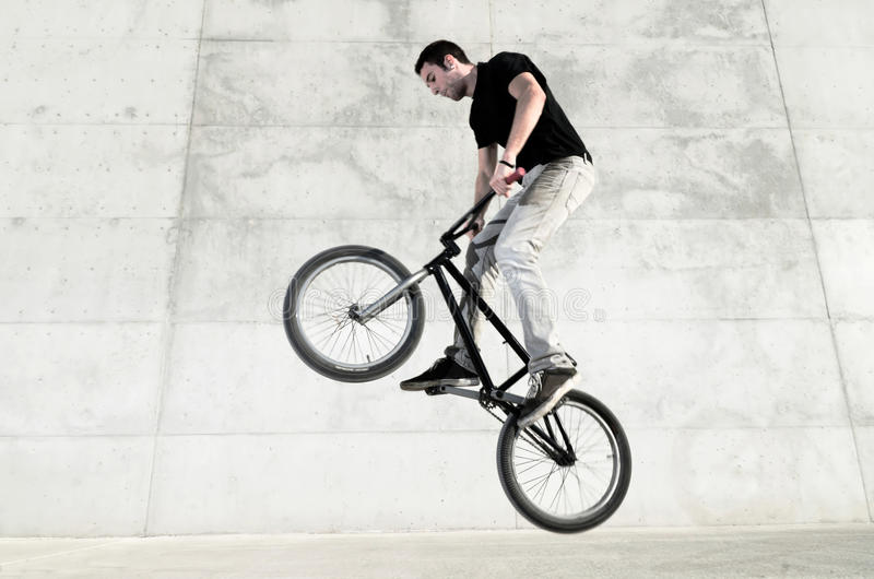 Young BMX bicycle rider. On a grey urban concrete background stock image