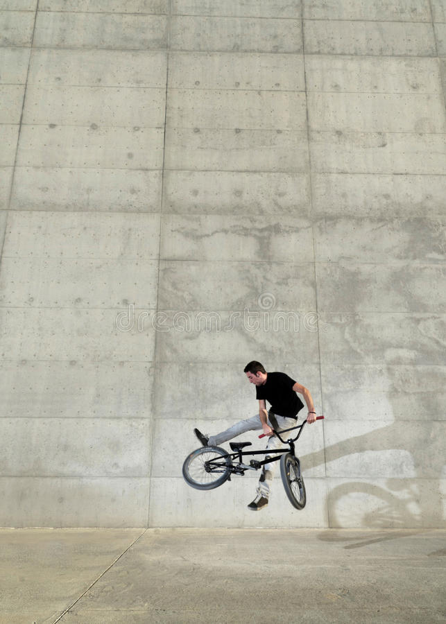 Young BMX bicycle rider. On a grey urban concrete background royalty free stock image