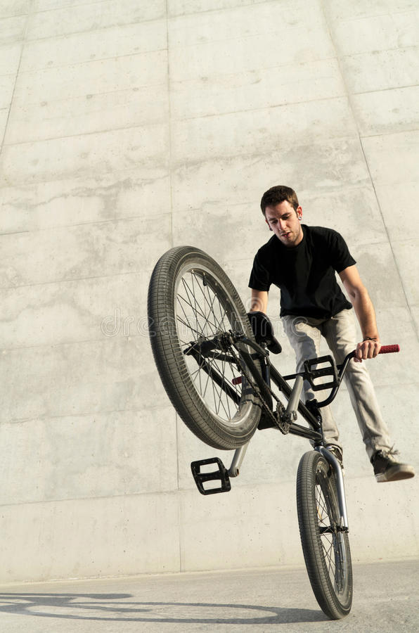 Young BMX bicycle rider. On a grey urban concrete background royalty free stock photos