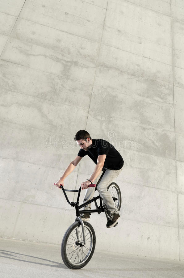 Young BMX bicycle rider. On a grey urban concrete background stock photography