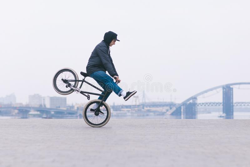 BMX bicycle rider rides on the front wheel against the background of the minimalistic urban landscape.BMX concept royalty free stock images